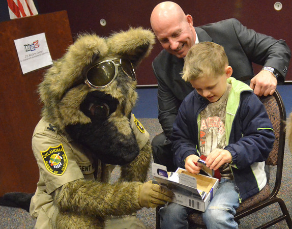 Oklahoma Bureau of Narcotics Director Darrell Weaver, left, and bureau mascot Agent Roz show Max Joyner one of the donated PSP Go gaming systems the bureau gave to the  J.D. McCarty Center on Wednesday.  <br /> Kyle Phillips/The Transcript