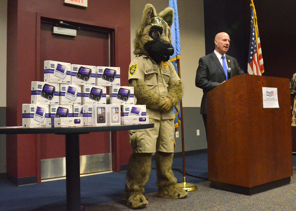 Oklahoma Bureau of Narcotics Director Darrell Weaver, right, speaks to the media as he and mascot Agent Roz donate 15 PSP Go gaming systems and two iPod Classics to the J.D. McCarty Center on Wednesday.  <br /> Kyle Phillips/The Transcript
