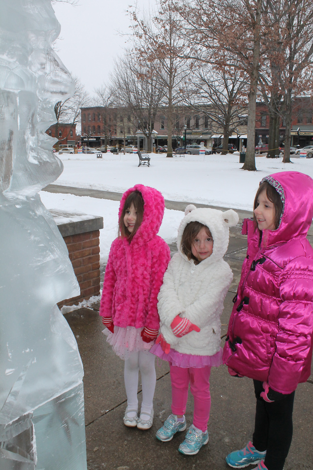 LAWRENCE PANTAGES / GAZETTE Sisters Julie, 5; Lily, 3; and Jane, 6, Wasowski of Medina came to Public Square on Friday afternoon after school with their mother Jenny to see some of the 80 pre-carved sculptures at the 22nd Ice Festival.