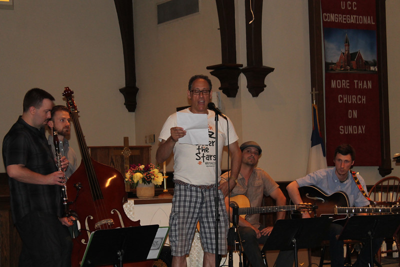 """LAWRENCE PANTAGES / GAZETTE The founder and executive director of the Ohio Regional Music Arts Cultural Outreach nonprofit, Tom Sigel, speaks to an audience of about 150 Saturday night as the program's first """"Jazz Under the Stars"""" event of 2016 had to be moved indoors to United Church of Christ Congregational at 217 E. Liberty St. in Medina. The Akron-based quartet Moustache Yourself played for two hours."""