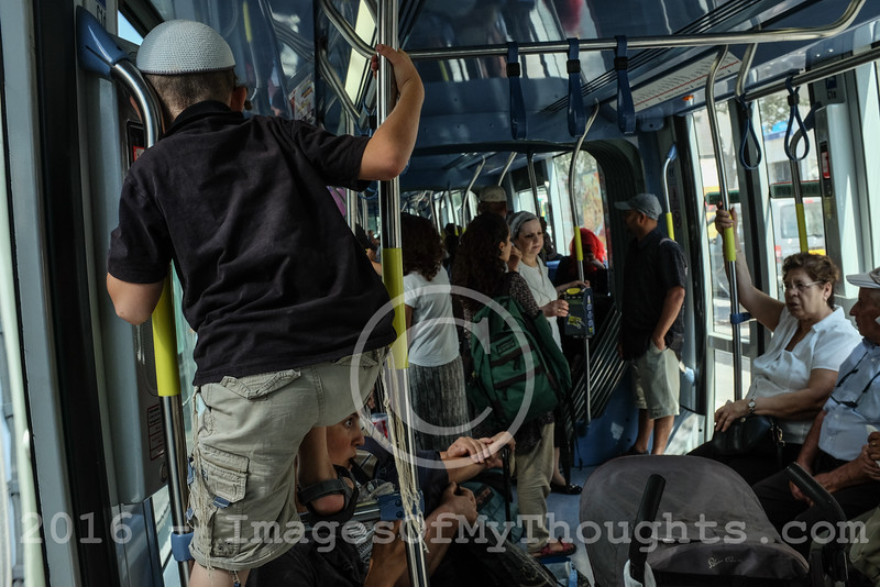 A young boy climbs the handrails on the Jerusalem tram