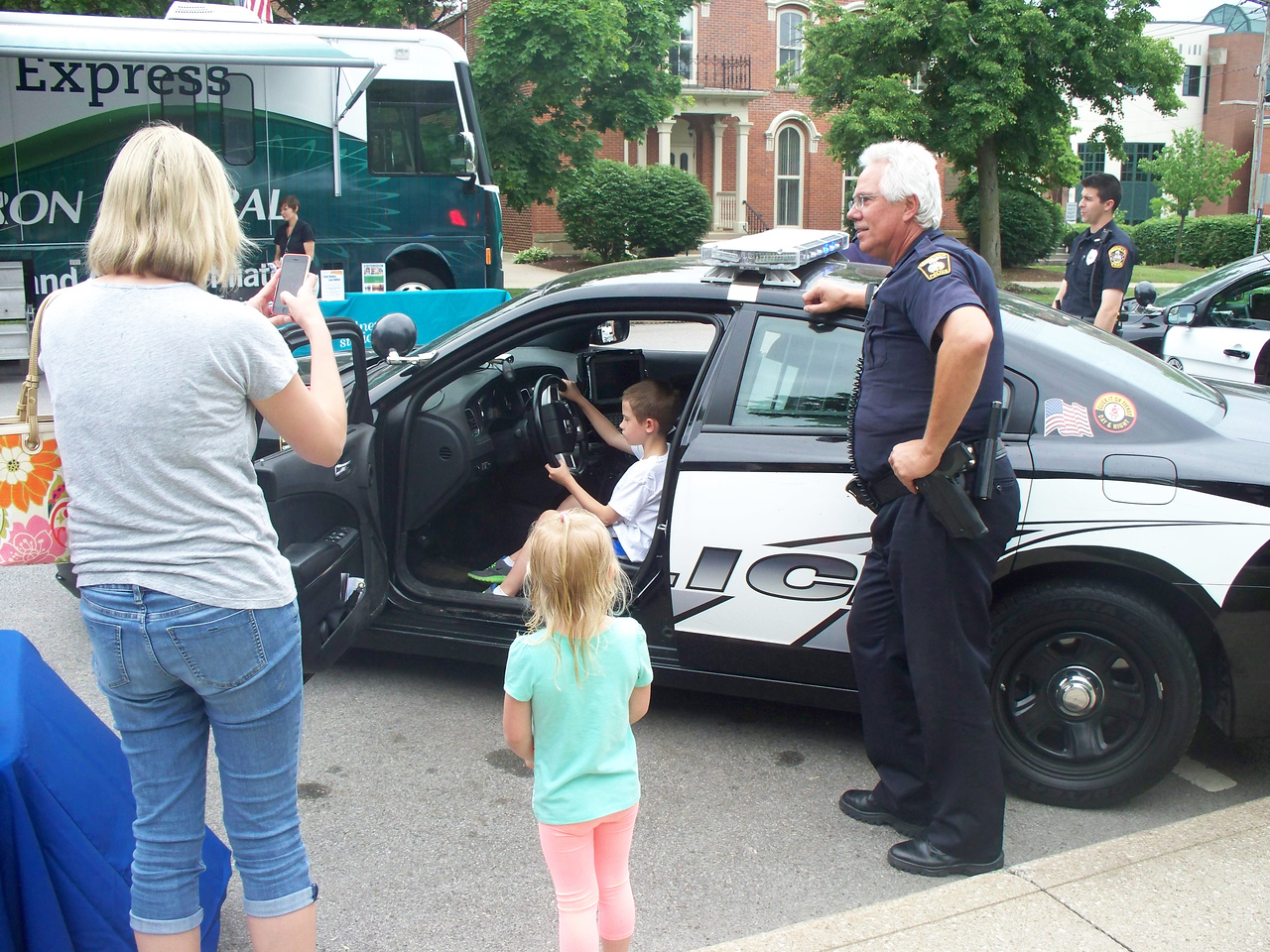 """NIKKI RHOADES / GAZETTE Mom Stephanie Shoemaker, of Medina, and sister Reagan Shoemaker look on as Brunswick Police Officer Steve Kartha shows his vehicle to Luke Shoemaker. The family attended the Kids Day of Safety & Play for the first time. Stephanie said of the event, """"It's a lot of fun — great for kids and families."""""""