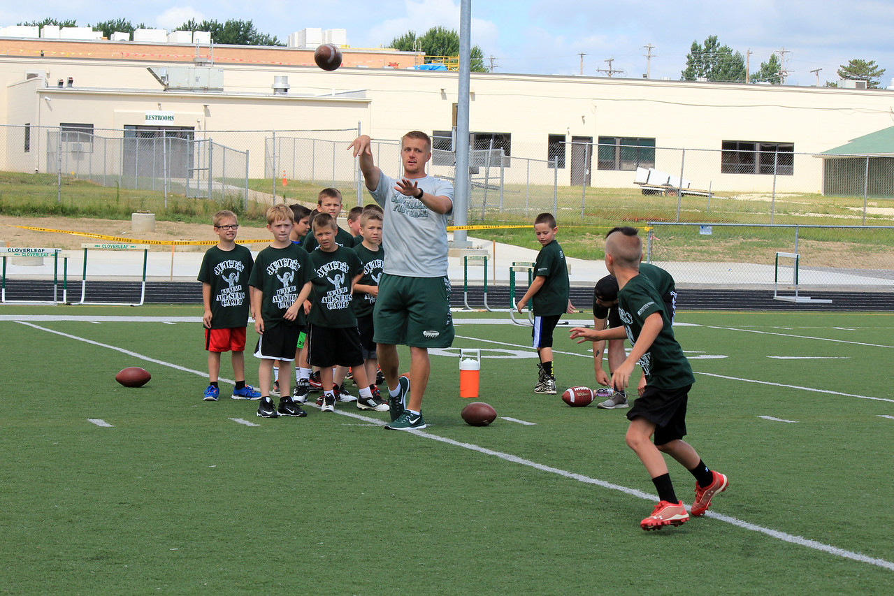 HALEE HEIRONIMUS / GAZETTE Cloverleaf head football coach Justin Vorhies runs an offensive drill with the campers during Juice's All-Star Camp Saturday morning.