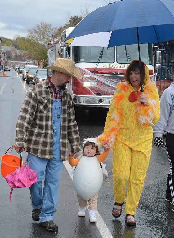 . Dressed as a farmer, a chicken and an egg, Jim and Heather O\'Brien and their daughter Hadlee, 1, march along Park Street in Adams for the Adams Lions Club\'s annual Halloween Parade. Sunday October 30, 2016. Gillian Jones � The Berkshire Eagle