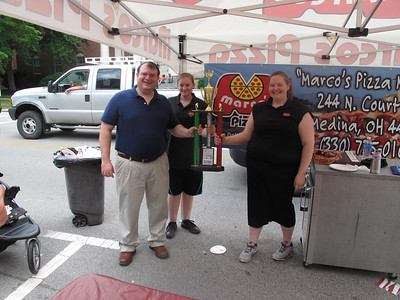 BOB FINNAN / GAZETTE Marco's Pizza was the winner of the judges' award in the Pizza Palooza Saturday on Public Square in Medina. Pictured are Sen. Larry Obhof, left, employee Breanna Opgenorth and general manager Tracy Fox.