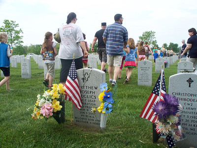 NIKKI RHOADES / GAZETTE Many graves at a Saturday decorating event at the Ohio Western Reserve National Cemetery in Rittman already had displays with patriotic themes. Shown is the marker for Matthew Kuglics, of Green in Summit County. Kuglics was killed in service in Iraq in 2007.