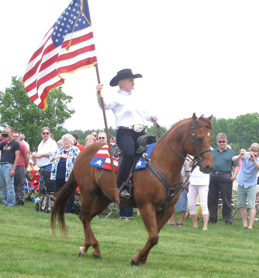 ELIZABETH DOBBINS / GAZETTE Shan Hough, a member of Northern Oho Outlaws Cowboy Mounted Shooting Association, carries an American flag during the posting of colors at the Ohio Western Reserve National Cemetery in Rittman Sunday.