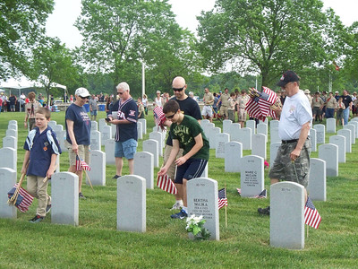 NIKKI RHOADES / GAZETTE Hundreds of volunteers helped decorate the graves on Saturday in preparation for Memorial Day at the Ohio Western Reserve National Cemetery in Rittman.
