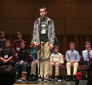 "ASHLEY FOX / GAZETTE Alex Holthouse, a seventh-grade student from Claggett Middle School, appears at the microphone Saturday during the 2017 Akron Regional Spelling Bee. Holthouse reached the fourth round before missing ""chary."""