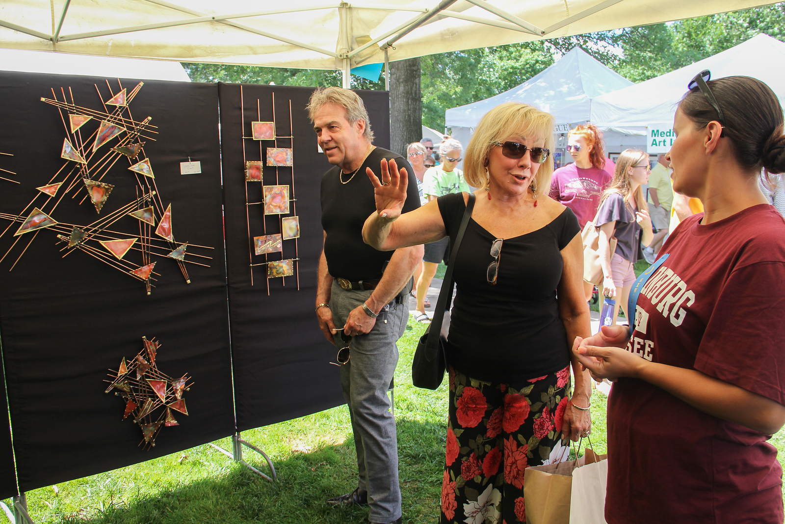 ALEC SMITH / GAZETTE Mark Overholt with his wife Sherry Overholt from Medina talk with Alicia Poff (right) on Sunday during the Art in the Park festival on Public Square in Medina. Poff is from Poff Sculptures in Columbus.