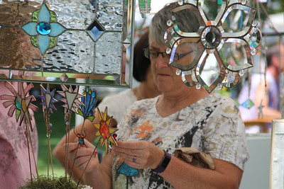 ALEC SMITH / GAZETTE Deb Rauschenberg from Wooster looks at frog and bird ornaments, shown by Christy Hink on Sunday at the Art in the Park show held Sunday on Public Square in Medina.
