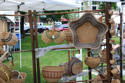 LUCAS FORTNEY / GAZETTE Janet Brim's baskets hang on display at a booth Sunday on Public Square during the Art in the Park juried show. The baskets are characterized by non-traditional color choices and patterns.