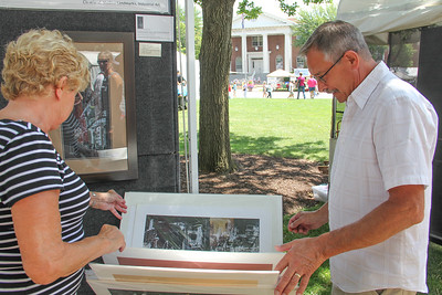 ALEC SMITH / GAZETTE Dagmar Howman and her husband Mike Howman from Seville look at fine art by Paul G. Jira on Sunday during Art in the Park on Public Square in Medina.