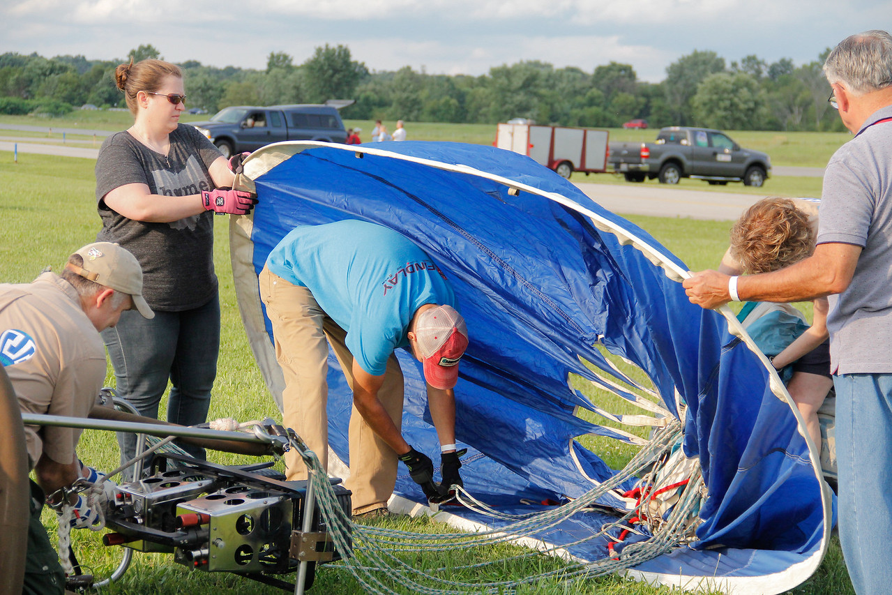 ALEC SMITH / GAZETTE A crew of balloonists works Saturday on their equipment at Wadsworth Municipal Airport before threatening weather canceled a launch that more than 1,000 people came to watch. Shown at near the engine is Denny Helmuth from Wooster; in the middle working on the ropes is Dick Frase from Massillon; on the left at rear is Tracie Schmolt from North Canton and at right rear is Kathy Helmuth, Denny's wife. At right is sponsor Ron Palitto.