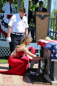HALEE HEIRONIMUS / GAZETTE Brunswick Summer Celebration Queen Faith Bedenik places a wreath by the graveside at Westview Cemetery during a Memorial Day cemetery. She was escorted by a member of Brunswick Veterans of Foreign Wars post 9520.