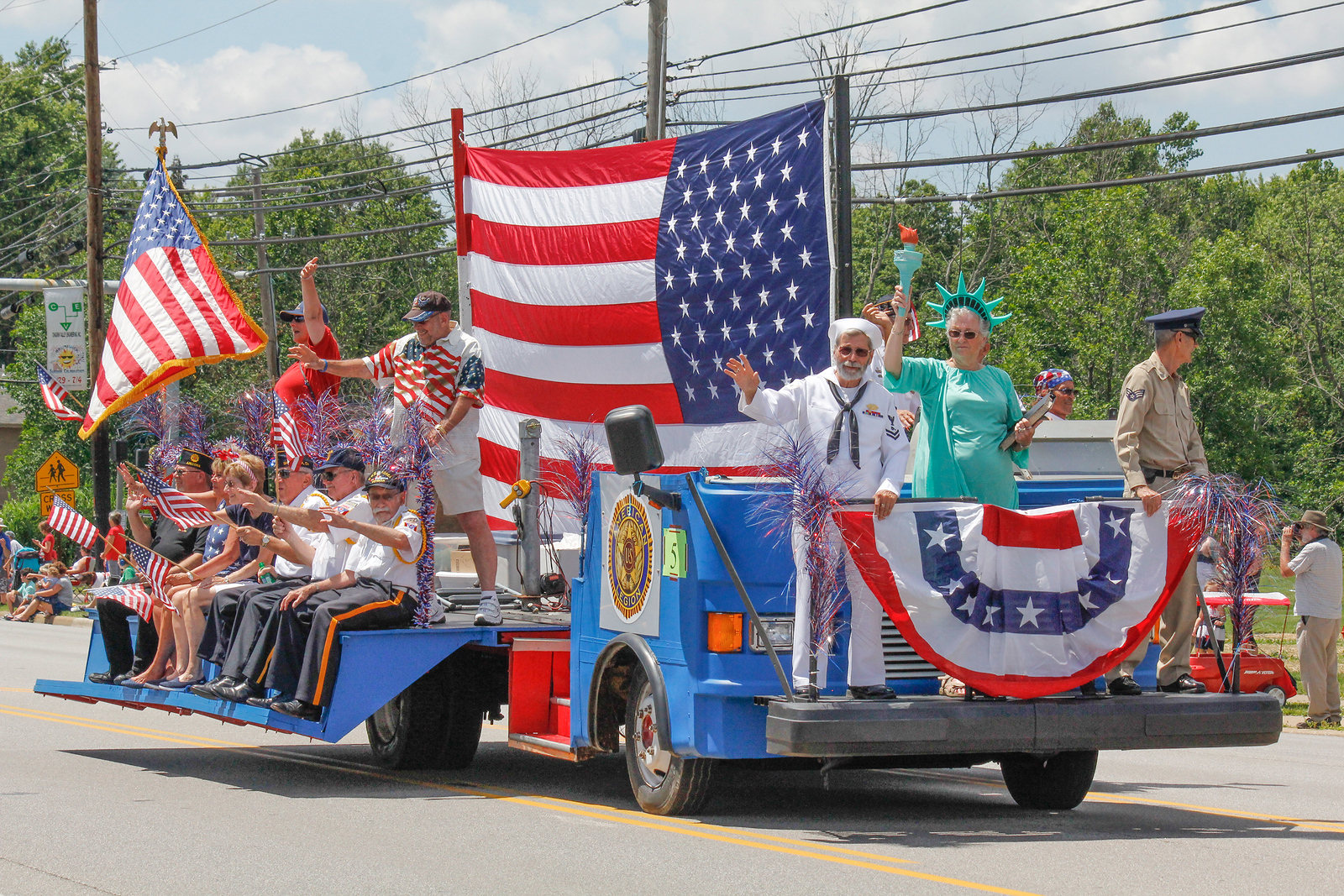 ALEC SMITH / GAZETTE A float is shown Sunday in the July 4 holiday weekend parade held on Center Road (state Route 303) in Brunswick as part of the city's Summer Celebration. Shown at left in the American flag T-shirt is Dave Hayes of Hinckley Township, an Air Force veteran. In the sailor uniform is Tom Bizzi from Brunswick, a veteran of the Navy. Shown as Miss Liberty is Barb Hayes of Hinckley, the wife of Dave Hayes. Shown on the corner on the right is Ralph Johnson of Hinckley Township, an Air Force veteran. Driving the float in the back in the red hat is Bob Prevost, an American Legion Post 234 Commander from Brunswick.