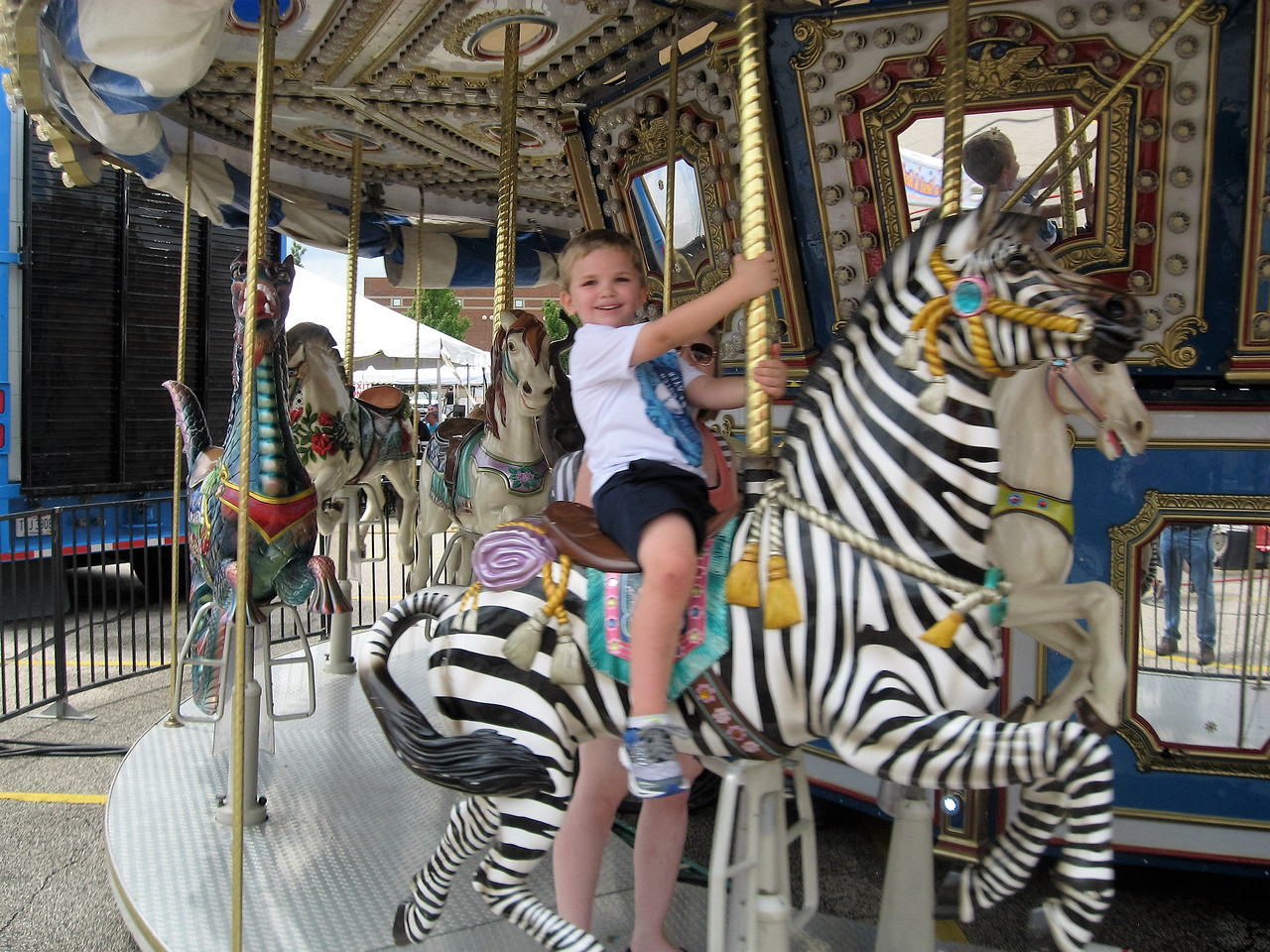 BOB SANDRICK / GAZETTE Caleb Langos, 5, of Wadsworth shows his excitement while riding the merry-go-round Saturday at the 2017 Summer Celebration in Brunswick. His mom Lisa Langos, hidden in the photo, rides with him.