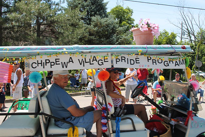 LAWRENCE PANTAGES / GAZETTE Members of the Chippewa Lake Village Pride program ride Tuesday in a July 4 parade. The volunteers work on beautification projects such as placing flower pots in the village. The group is headed by Pam Williams (driving the cart).