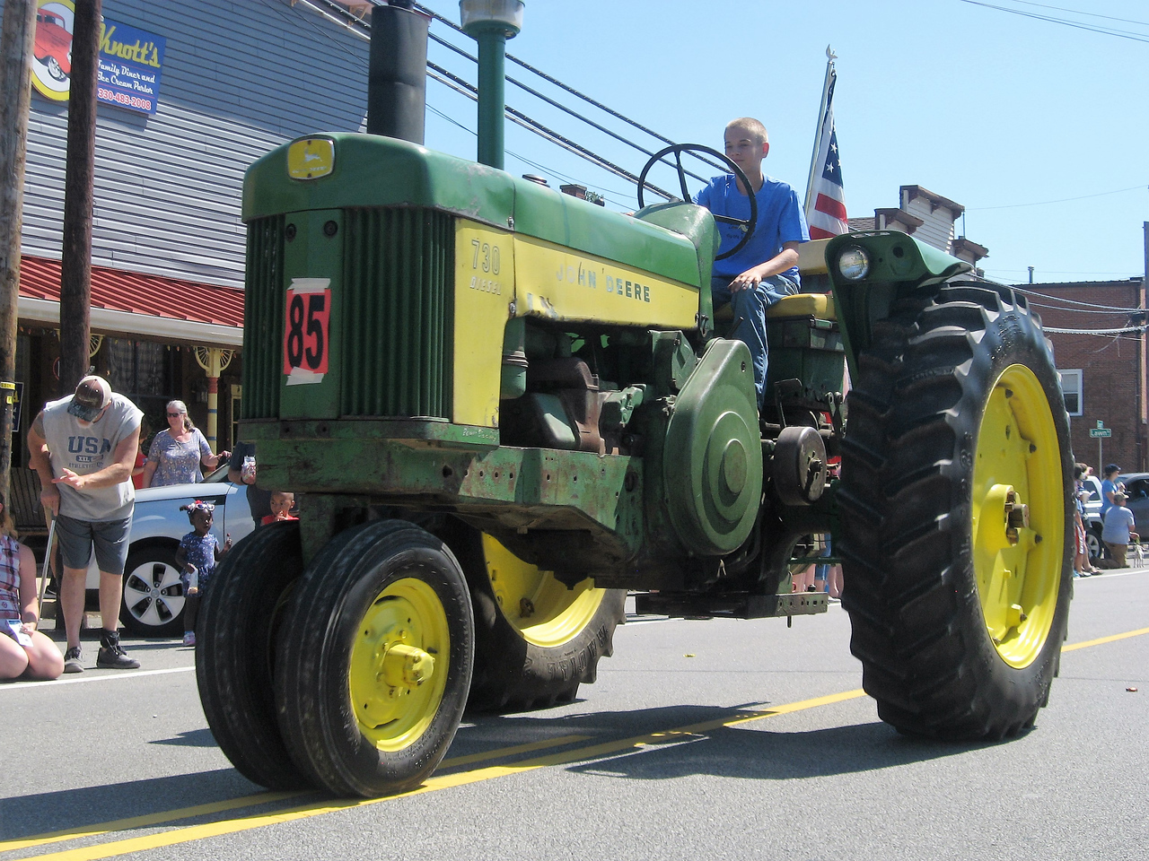 BOB SANDRICK / GAZETTE This giant tractor had a tiny driver Tuesday morning in the Liverpool Township Fourth of July parade.