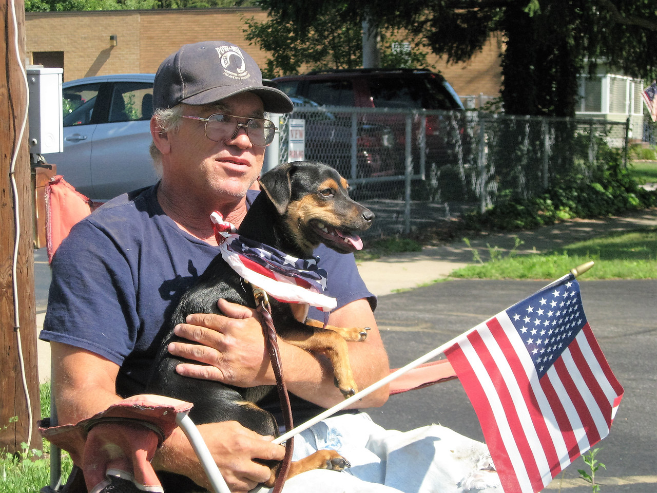 BOB SANDRICK / GAZETTE John Rowen and his buddy Louie, who's only about 6 months old, found a good spot for Tuesday's Fourth of July parade in Liverpool Township. Rowen and Louie live in Columbia Station.