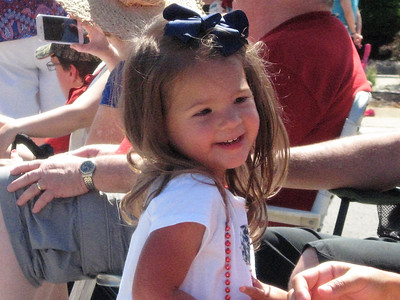 BOB SANDRICK / GAZETTE Gabriella Glaser, 2, of Brunswick Hills wore a beaded necklace she caught Tuesday morning in the Liverpool Township Fourth of July parade. Her mom, Maria, helped her put on the necklace.