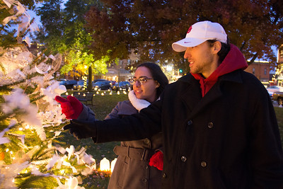 ALEC SMITH / GAZETTE Hunter Heaton, of Medina, and Golnar Pahldad, of Strongsville, place the name of Jake Vondervellen on the Tree of Light in Medina's Uptown Park on Sunday evening following the Candlelight Memorial Service organized by Waite and Son Funeral Homes during the city's 33rd annual Candlelight Walk.