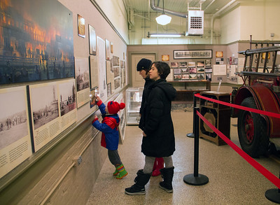 ALEC SMITH / GAZETTE Waiting for the Parade of Lights to begin on a rainy Saturday night in Medina, Deanne Hudak, her daughter, Peyton, and her nephew, Caleb Stoicoiu, 3, visit the Medina Town Hall and Engine House Museum on Public Square.