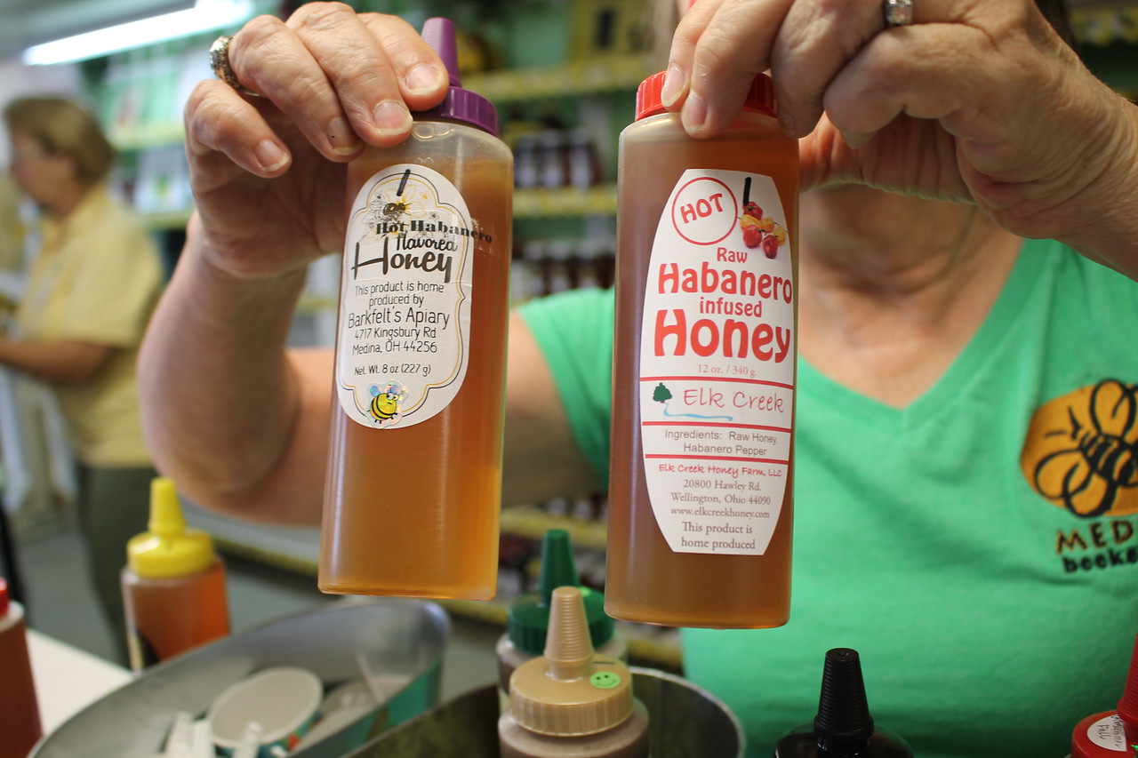 LAWRENCE PANTAGES / GAZETTE Kim Barkfelt of the Medina Beekeepers Association shows a hot habanero honey product that was for sale Monday on the first day of the 2017 Medina County Fair.