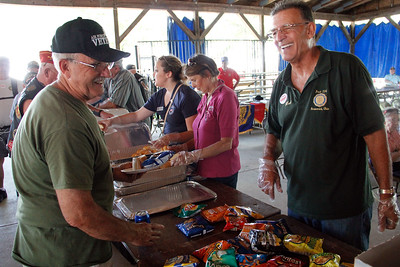 ALEC SMITH / GAZETTE Carl Hosey, left, an Air Force Veteran from Medina, passes Bob Prevost, commander of the Brunswick American Legion Post 234, while going down the food line Monday afternoon at the Medina County Fair.