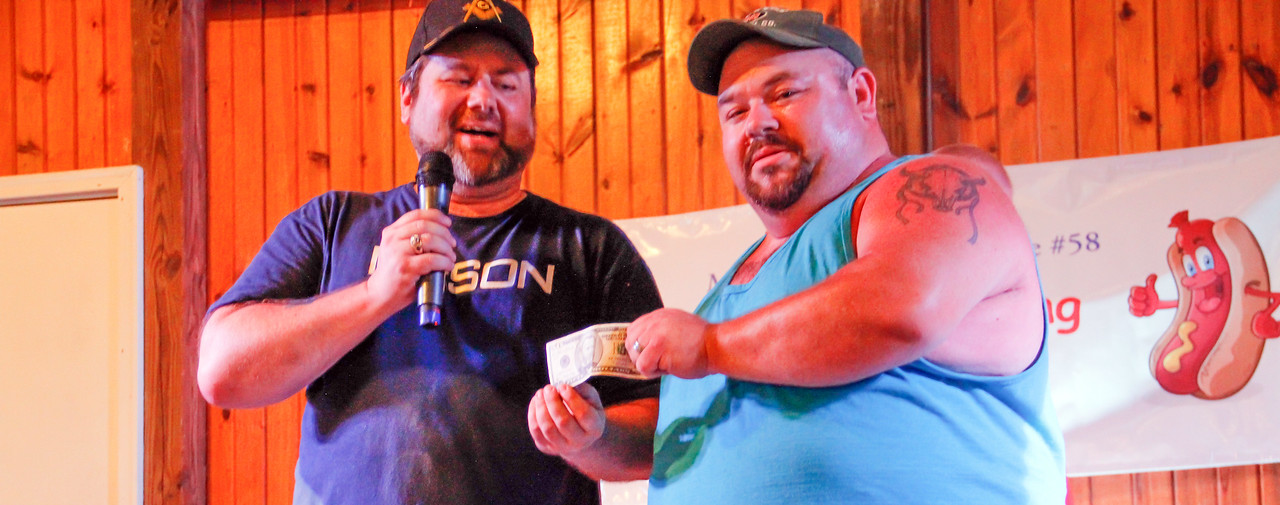 ALEC SMITH/GAZETTE Lodi resident Scott Lucas, right, is the winner of the men's division in the hot dog-eating contest Wednesday night at the Medina County Fair. Jim Huff, far right, from Parma, is the contest's announcer.