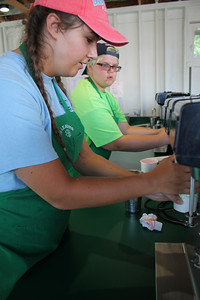 LAWRENCE PANTAGES / GAZETTE Emily George, a chairperson of the Junior Leaders group, prepares a milkshake Sunday for visitors to the milkshake booth on the day before the opening of the 2017 Medina County Fair. George is a Buckeye High School student from York Township. To her left is Jess Rennu of Liverpool Township, a Medina County Career Center student.