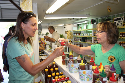 LAWRENCE PANTAGES / GAZETTE Pauline Patera of Brunswick Hills Township samples hot habanero honey from Kim Barkfelt, also of Brunswick Hills Township, on Monday during the first day of the 2017 Medina County Fair. Barkfelt was assisting in the Medina Beekeepers Association's vending booth.