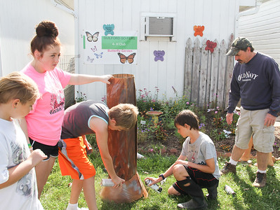 ALEC SMITH / GAZETTE The Litchfield Friendly Workers 4-H Club sets up Saturday at the Medina County Fair. From left are Elvira Winterstein of Brunswick, Gabrielle Lachance of Brunswick, Jacob Wetterman of Medina (spray painting the tree), Ben West and Jack West of Medina.