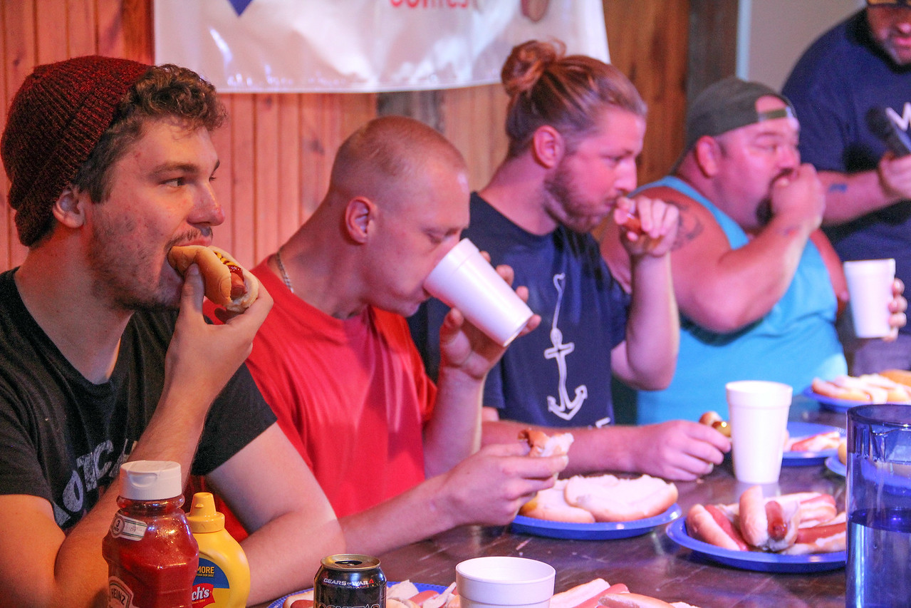 ALEC SMITH/GAZETTE Competitors in Wednesday night's hot dog-eating contest at the Medina County Fair are, from left, Taylor McKillen from Medina, Nathan Whitecotton from Akron, Lucas Hutchinson from New Jersey and Lodi resident Scott Lucas, the winner of the men's division. Jim Huff, far right, from Parma, is the contest's announcer.