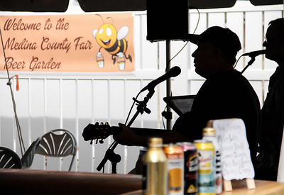 ALEC SMITH / GAZETTE The new Beer Garden at the Medina County Fair opens for the day at 4:30 p.m. Thursday with music by Mike Baker, front, and Tim Stacy of Wild Oats from the Akron-Canton area.