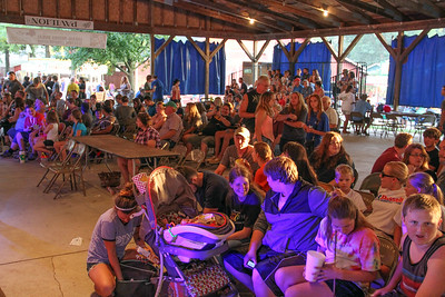 ALEC SMITH/GAZETTE Friends and family gather in the pavilion Wednesday night to watch the hot dog-eating contest at the Medina County Fair.