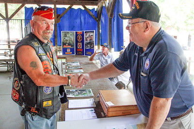 ALEC SMITH / GAZETTE Wally Ronsky, left, a U.S. Marine Veteran from Seville, talks with Rick Pethtel, of Medina, about the Vietnam War Monday at the Medina County Fair. Monday was dedicated as Veteran's Day.
