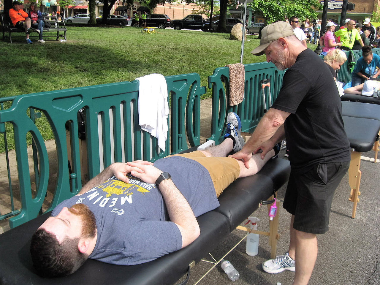 BOB SANDRICK / GAZETTE Runner Jared Anay of University Heights, who competed in a 5-kilometer race on Saturday in Medina, was rubbed down afterward by Roger Buttrick, a professional licensed massage therapist with Studio on Stone.