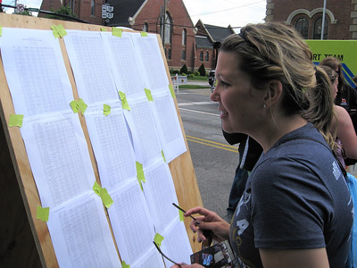 BOB SANDRICK / GAZETTE Tiffany Randall of Medina checks the winners list Saturday for results from the Medina Half Marathon.