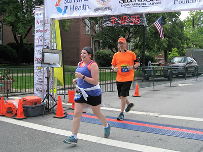 BOB SANDRICK / GAZETTE Heather and Gary Bush of Hartville cross the finish line Saturday at the Medina Half Marathon. It was Heather's first half-marathon.