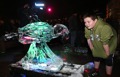 AARON JOSEFCZYK / GAZETTE Brandon Chaser of Medina looks at a winning sculpture Friday night at the 23rd Medina Ice Festival.