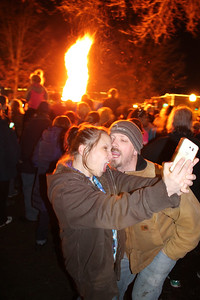 LAWRENCE PANTAGES / GAZETTE Jennie Mathews and Scott Hollandsworth, of Shreve in Wayne County, made faces for a selfie photograph with the fire and ice tower in the background Friday night during the 23rd Medina Ice Festival on Public Square. Mathews said she is a native of Medina.