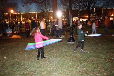 LAWRENCE PANTAGES / GAZETTE Cousins Sara Wolosyn, 7, and Olivia Wellman, 7, both of Medina, enjoyed playing with glowsticks Friday night during the first day of the 23rd Medina Ice Festival on Public Square. Both Sara and Olivia are students at Ella Canavan Elementary School.