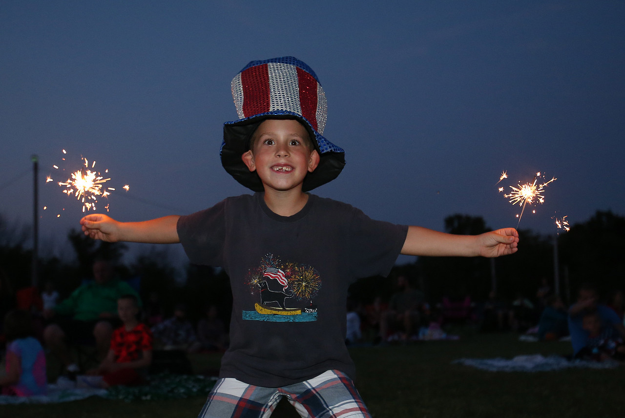 Logan Falatach plays with sparklers prior to the fireworks show in Medina. Aaron Josefczyk/Gazette