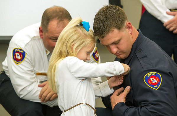 Lillyann White pins a badge on her father, Daniel White as Joplin Fire Chief James Furgerson looks on during the Joplin Fire Department's Recruit Graduation and Promotion Ceremony on Friday at the Joplin Public Safety Center. White was one of five new firefighters who completed their training and will begin service to the community. Other graduates are: Baylor Smith, Kent Shouse, Davis Martin and Jason Levi McBryde - a second generation firefighter.<br /> Globe | Laurie Sisk