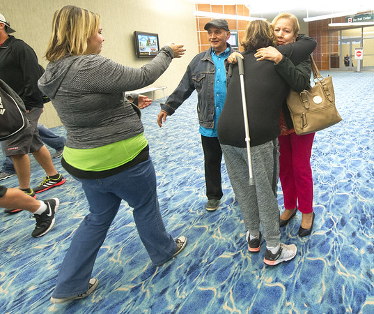 From the left: Syleris Gwin Martinez extends her arms for a hug from her grandfather, Raul Martinez as Irelys Martinez embraces her mother, Oraida Muñoz, upon Raul and Oraida's arrival from Puerto Rico on Tuesday morning at the Springfield-Branson National Airport.<br /> Globe | Laurie Sisk