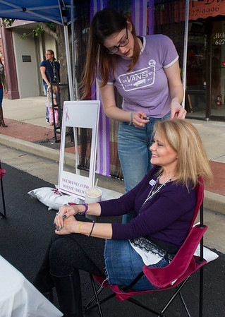 Lafayette House volunteer Lyndsey Pauley attaches a strand of purple hair to Kayla Pekarek's hair during a fundraiser for Lafayette House on Third Thursday in Downtown Joplin.<br /> Globe | Laurie Sisk