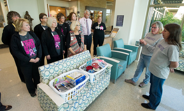 Anne Jiles, second from the right and Dixie Buerge, far right, both General Mills second shift workers, talk Friday about the scores of comfort items they collected from coworkers for patients at the Mercy Cancer Center as center staff listen. Items collected included puzzle books, pens, snacks, blankets, gloves for using cell phones and more.<br /> Globe | Laurie Sisk