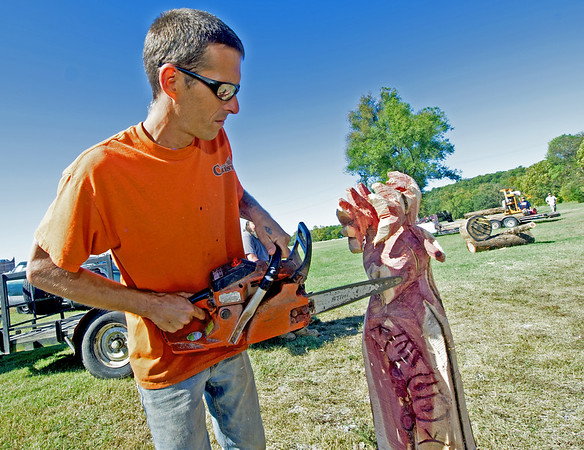 Darick Rice, of Carving for Christ, uses a chainsaw to carve a deer head during Neosho's Fall Festival on Saturday at Morse Park.<br /> Globe | Laurie Sisk