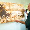 """Veterinarian and artist Michael Gory hangs his acrylic piece, """"Awakening"""" at his College View Veterinary Clinic on Tuesday. <br /> Globe 